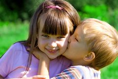 Kiss. Sister with brother on a meadow Stock Images