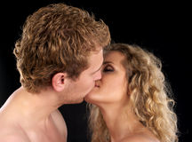 Kiss. Beautiful young couple kissing, black background Royalty Free Stock Photos