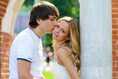 Kiss. Under the arches of brick picture boy kissing a girl with long blond hair Royalty Free Stock Images
