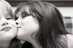 Kiss. Two little girls sharing a cuddle and a kiss royalty free stock photography