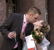 Kiss. Ing newlyweds in front of th civil registry office royalty free stock image