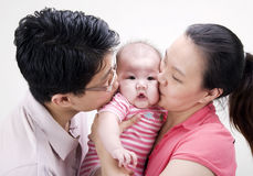 Kiss. Asian parent kissing their 4 months old baby girl Royalty Free Stock Photos
