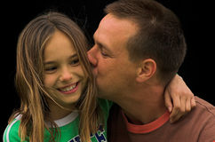 A Kiss. A father kissing his daughter on the cheek royalty free stock image