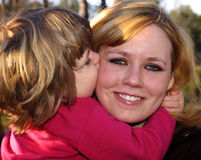Kiss. Little girl giving mother a big kiss on the cheek Royalty Free Stock Image