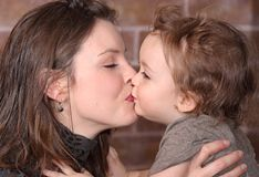 Kiss. Mother kissing is baby in home Stock Images