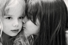 Kiss. A little girl giving a kiss to her sibling royalty free stock image