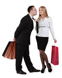 Kiss. Image of a young couple with shopping bags having fun while the women pulls her boyfriend tie for a kiss Stock Photos
