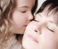 Kiss. Child kissing her mother Royalty Free Stock Photography