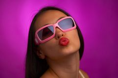 Kiss. Glamour portrait of young brunette in pink sunglasses giving a kiss Stock Photos