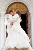 Kiss. Just married - young couple kissing beside the church Royalty Free Stock Image