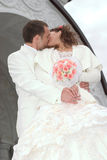 Kiss. Just married - young couple kissing beside the church Royalty Free Stock Photo