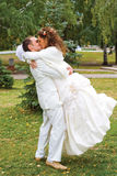 Kiss. Young couple in wedding wear with bouquet of roses kissing Royalty Free Stock Photos