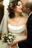Kiss. Just married young couple in wedding wear with bridal bouquet. Special toned photo f/x Stock Image