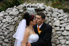 In the kiss. Groom kissing the bride in front of waterfall Royalty Free Stock Photography