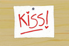Kiss!. Panel wood with a white ticket displayed, and on which 'designed the word kiss Stock Images
