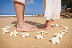 Kiss on the beach. Heart of white frangipani flowers in the sand. Feet male and female within the heart Stock Photo
