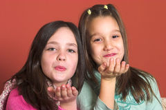 Kiss and blow. Two young girls sending kisses to the viewer Stock Photos