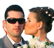 Kiss of the bride. The girl-bride kisses the guy-groom in sunglasses Stock Image