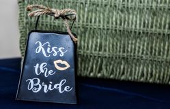 Kiss the Bride Cowbell. Instead of clinking glasses with knives, just ring the cowbell and the groom kisses his new bride stock image