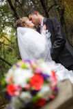 Kiss bride and groom in the autumn park. In their wedding day Royalty Free Stock Images