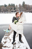 Kiss bride and groom on walk in winter. Bride and groom walking in winter in wedding day Royalty Free Stock Photo