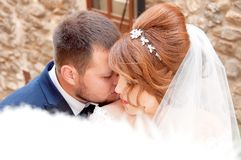 Kiss of the bride and groom. Wedding shot in the old town.  Warm Stock Photos