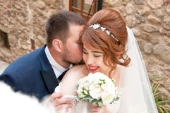 Kiss of the bride and groom. Wedding shot in the old town.  Warm Royalty Free Stock Image