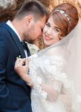 Kiss of the bride and groom. Wedding shot in the old town.  Warm. Embraces and gentle touches Royalty Free Stock Photo