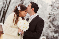 Kiss of bride and groom. In winter forest Stock Photo
