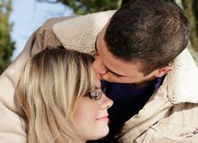 Kiss on brow. Couple in love, outdoor shot of two young people, the man kisses the woman on the forehead Royalty Free Stock Photos