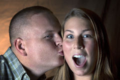 Kiss on the Cheek. A men kissing a girl on the cheek.  Girl has a shocked expression Royalty Free Stock Image