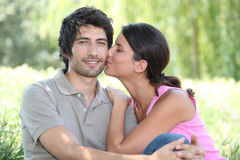 Kiss on the cheek. Whilst sat in a park Royalty Free Stock Images