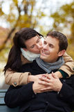 Kiss on the cheek in autumn. Women in love kissing happy men in park on cheek Royalty Free Stock Photography