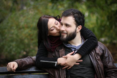 Kiss on the cheek. Young couple in a park sharing a romantic moment, when the girl gives a kiss on the cheek to the man, who is sitting on a bench stock images