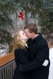 Kiss for Cupid. A young couple shares a kiss under cupid outdoors in the winter stock photo