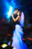 Kiss and dance young bride and groom. In dark banqueting hall Stock Photos