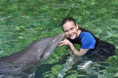 Kiss from a Dolphin !. Woman holding and getting a kiss from a dolphin Royalty Free Stock Photo