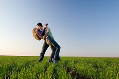 Kiss in the field. The guy and the girl kiss in a spring field Stock Images