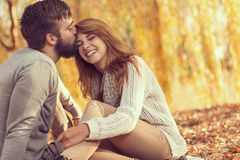 Kiss the girl. Couple in love sitting on autumn fallen leaves in a park, enjoying a beautiful autumn day. Man kissing a women in a forehead Royalty Free Stock Photos