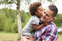 Kiss from the girl to her dad. Blank father with his african daugther having a nice time stock photo