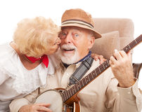 Kiss for Grandpa. Senior man playing banjo for his lady is rewarded with a kiss Royalty Free Stock Photography