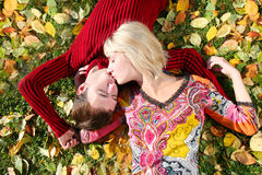 Kiss on a grass. Young beautiful couple is laying on the autumn grass Royalty Free Stock Images