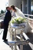 Kiss of the groom and bride. Wedding bouquet against kissing the groom and the bride royalty free stock images
