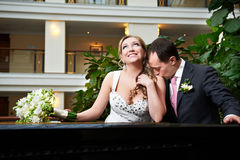 Kiss happy bride and groom in interior of hotel Royalty Free Stock Image