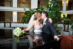 Kiss happy bride and groom in interior of hotel Royalty Free Stock Images