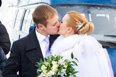 Kiss happy bride and groom on winter day Stock Photography