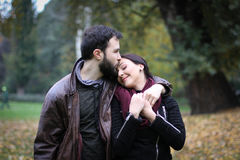 Kiss her on the forehead. Young couple in love having a date in the park. The men gives a kiss to his girlfriend on her forehead. He loves her, and she is stock photo