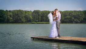 Kiss on a Lake jetty. The groom holds the bride on hands. A happy newly-married couple on river jetty Stock Photo
