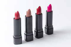 Kiss. 4 lipsticks lined up against white background Royalty Free Stock Photos