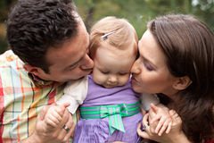 Kiss of love - parents with their baby girl Royalty Free Stock Images